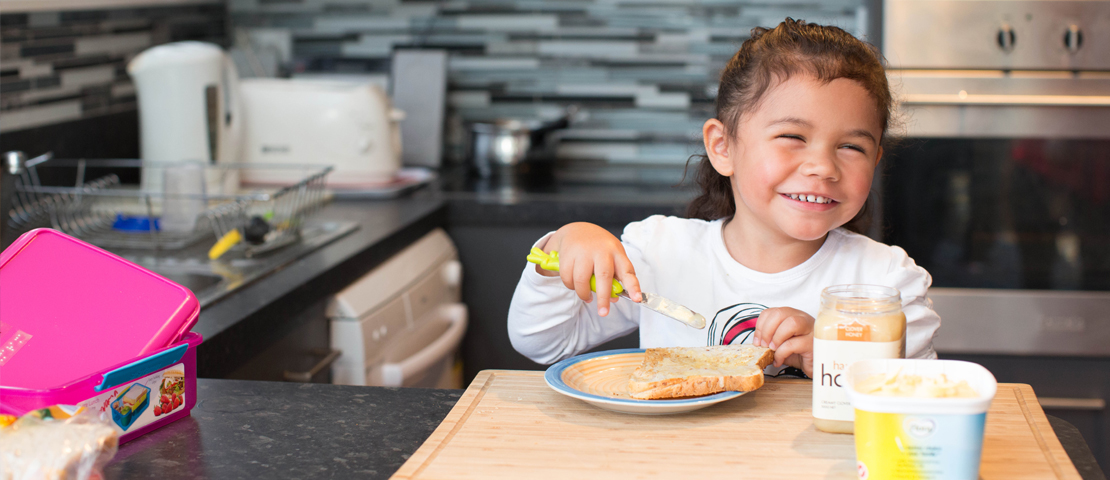 A young girl making toast