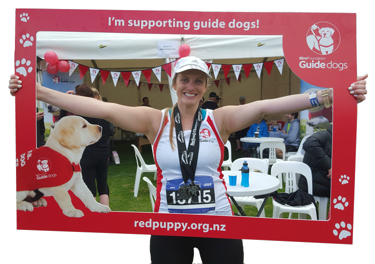 Auckland Marathon runner holding up the team guide dogs frame