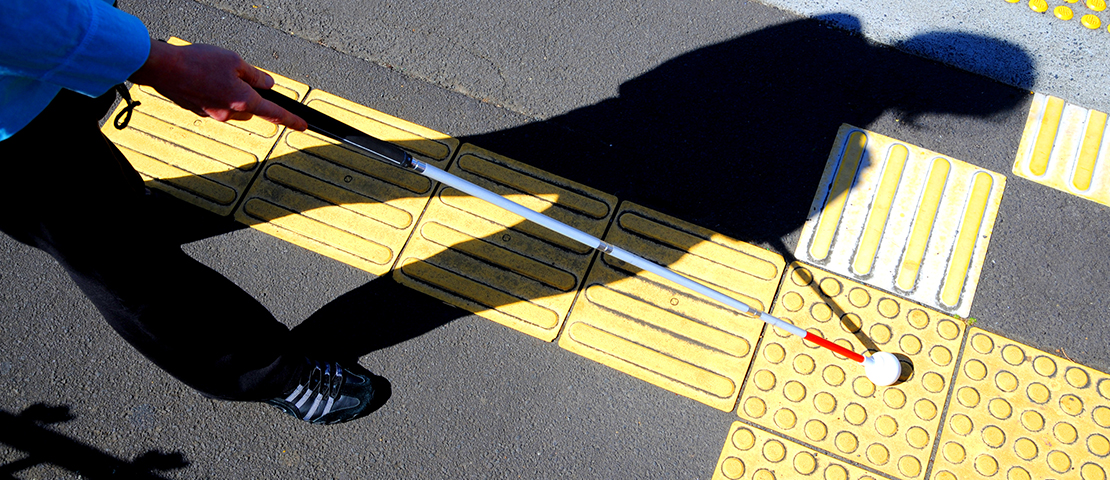 A man walking along the foot path with a white cane