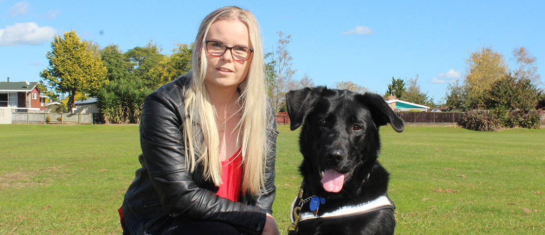 A young woman with her black Labrador guide dog