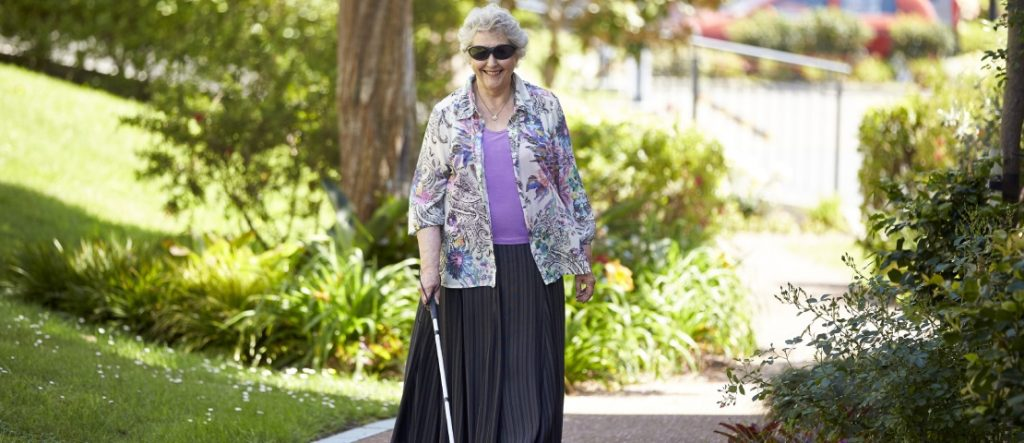 Woman walking with a white cane.