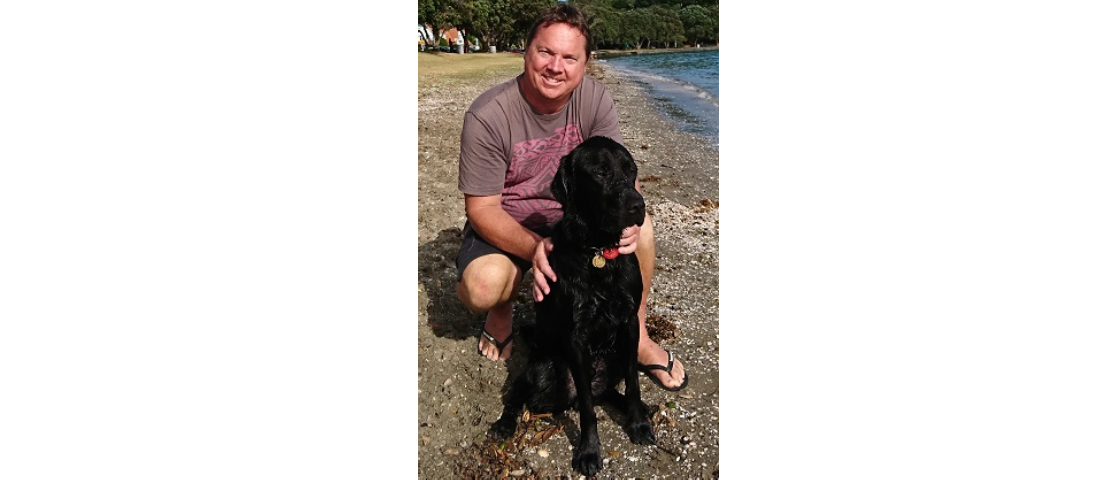 Geoff Laws and a black Labrador at the beach.