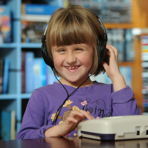 A girl wearing headphones and listening to a talking book