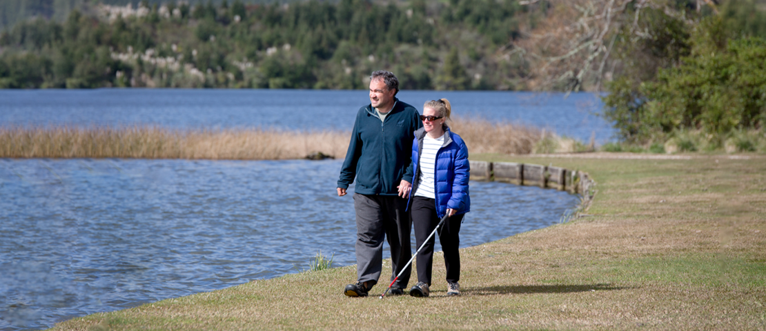 Holly, with her white cane, takes a walk with her husband beside a lake on a sunny day.